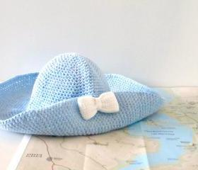 Crochet sun hat with wide brim and bow brooch in sky blue.
