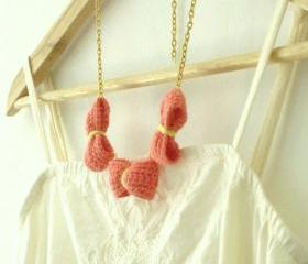 Three crochet bows necklace. Coral pink, golden chain.