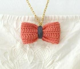Crochet bow pendant. Coral pink and grey cotton yarn.