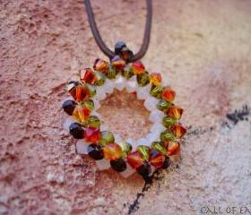 Beadwoven round pendant tangerine green burgundy white swarovski crystals. Tribal influence.