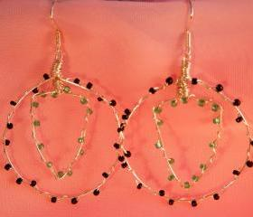 Wire hooped earrings with seed beads. hooped outer and shield shaped inner, opaque black and matt green seed beads. handmade.