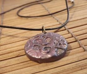 Polymer clay pendant in a circle shape on a leather cord thong, mica powder decoration.