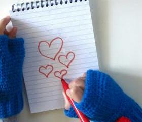 Oliver Twist,wrist high crochet fingerless mittens with removable pom-pom brooch in blue.