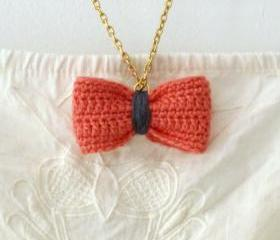 Crochet bow pendant. Salmon pink and grey cotton yarn.