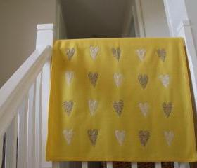 yellow baby blanket with sewn on hearts