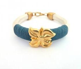 pearl white thick leather bracelet with a gold plated flower charm and dark teal waxed cotton cord details