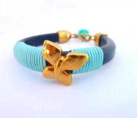 blue thick leather bracelet with a gold plated butterfly and light bue waxed cotton cord