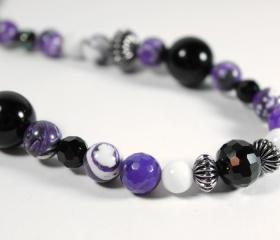 long beaded necklace in purple black and white