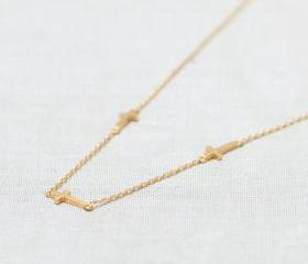 Three tiny Sideways Cross Necklace in gold