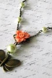 Romantic antiqued bronze butterfly necklace with greenish glass pearls and light orange resin flower