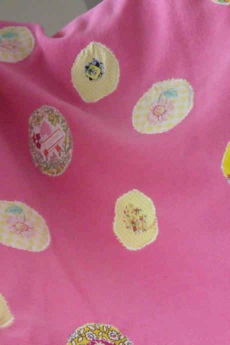pink baby blanket with yellow and cream circles